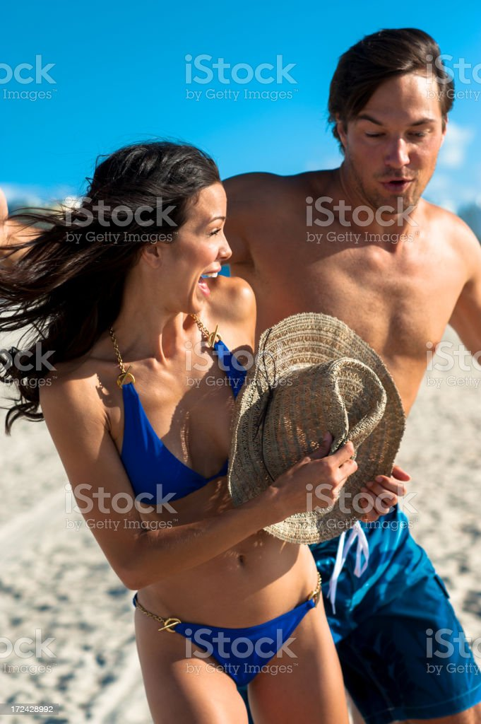 Young Couple Man and Woman Playing in Surf at Beach royalty-free stock photo
