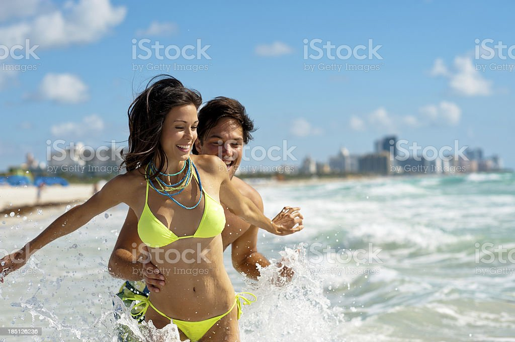 Young Couple Man and Woman Playing in Surf at Beach stock photo