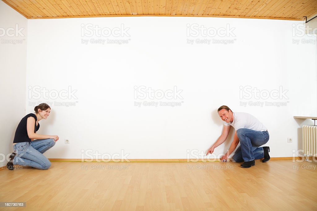 young couple measuring the rooms in their new apartment royalty-free stock photo