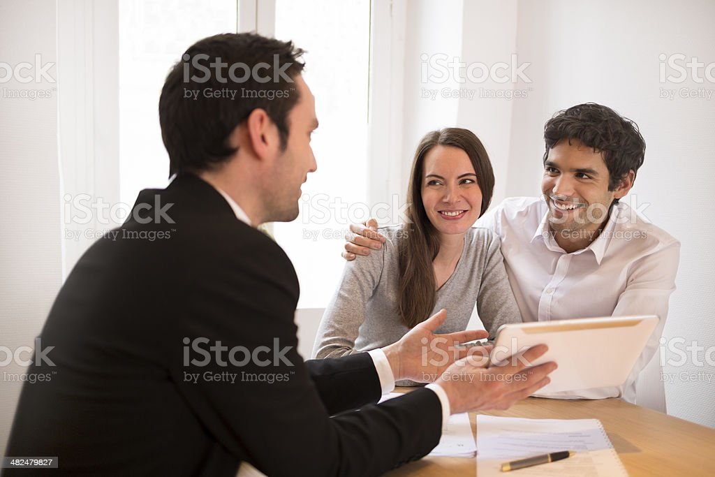 Young Couple meeting real-estate agent to buy property, presentation tablet stock photo