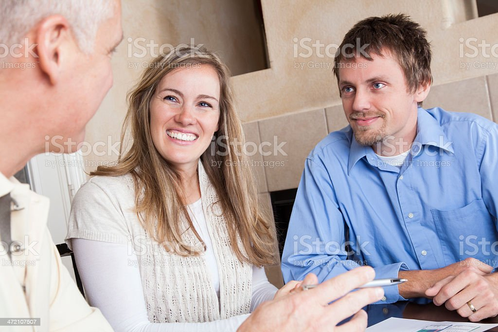 Young couple meeting with financial advisor or mortgage broker stock photo