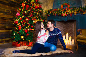 Young couple near fireplace celebrating Christmas