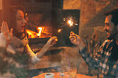 young couple near fireplace with sparkles