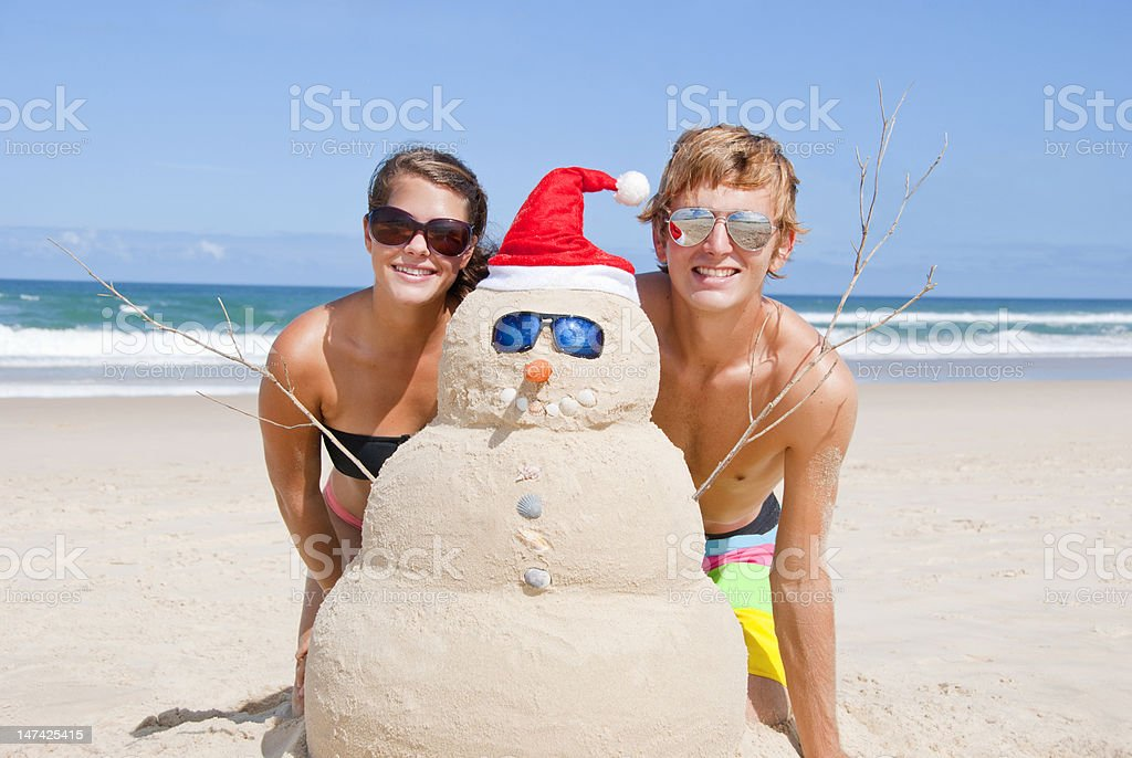 A young couple next to a sand snowman with Santa clause hat stock photo