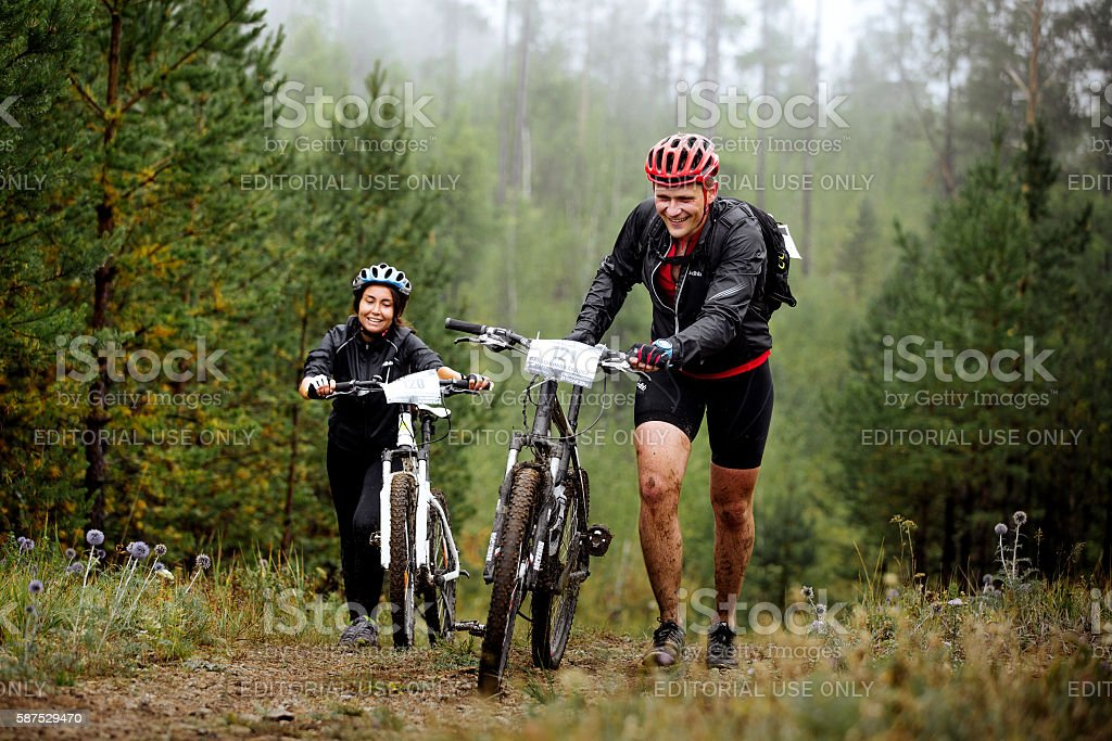 young couple of cyclists go uphill with your mountainbike royalty-free 스톡 사진