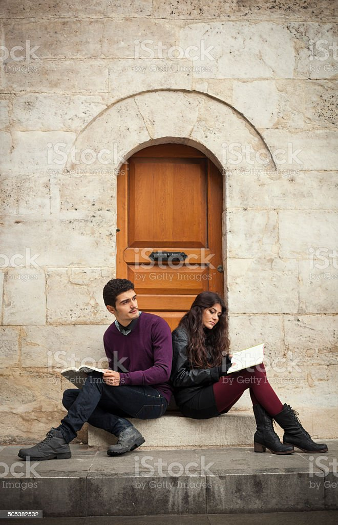 Young Couple of Travellers Reading Outside Their Apartment stock photo