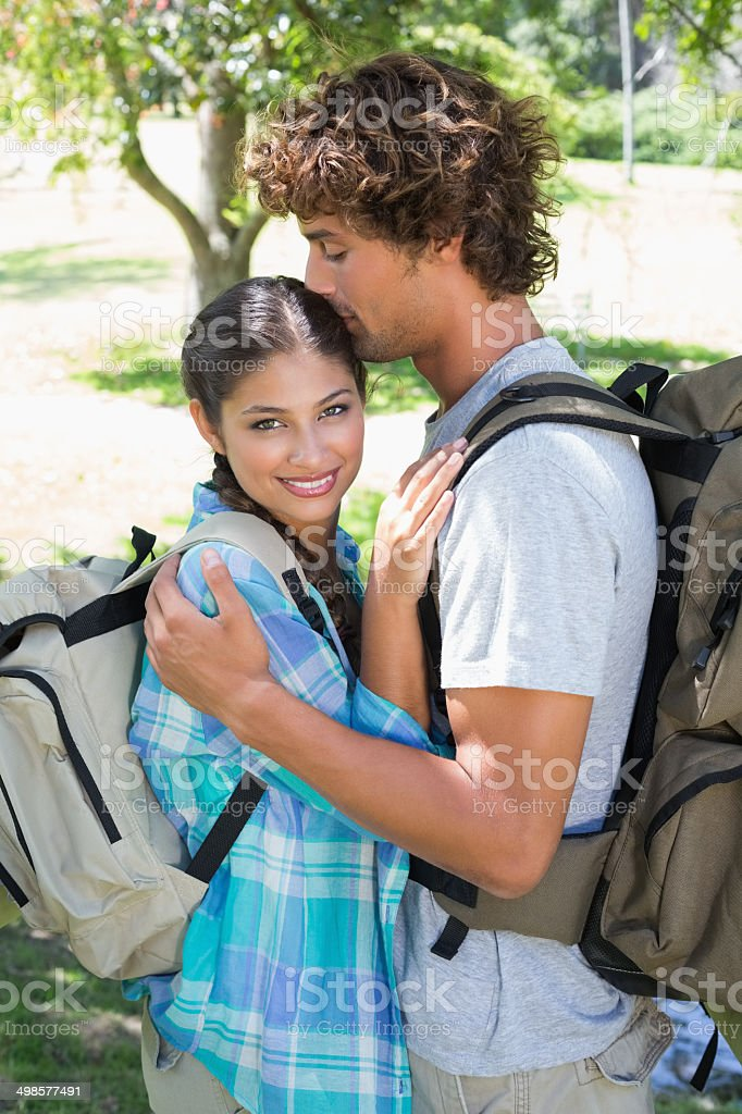 Young couple on a hike standing and embracing stock photo