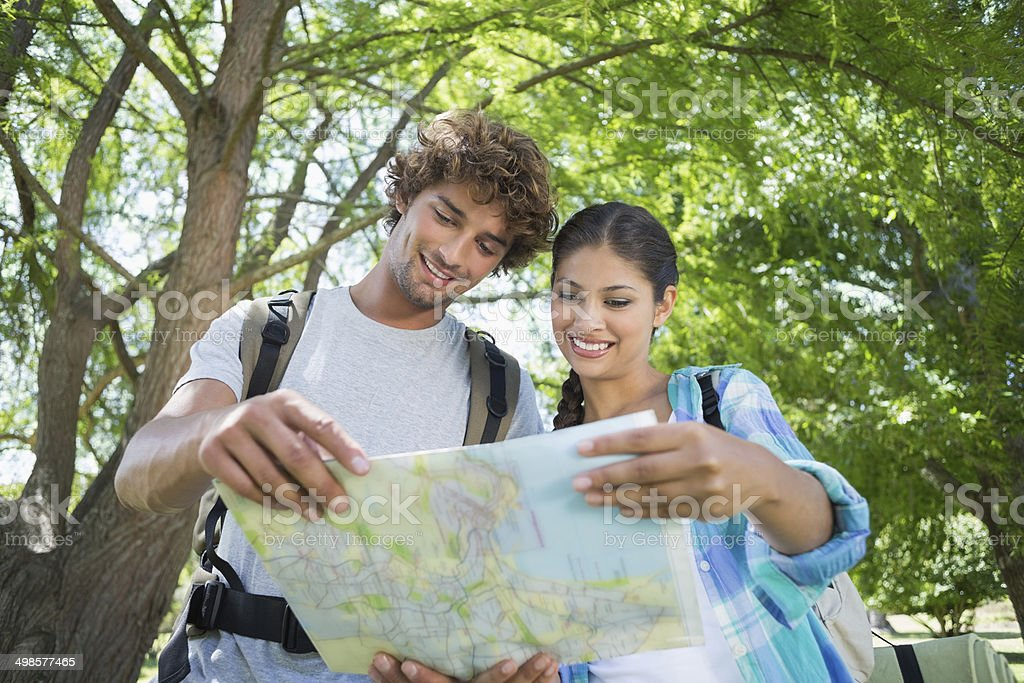 Young couple on a hike standing and reading map stock photo