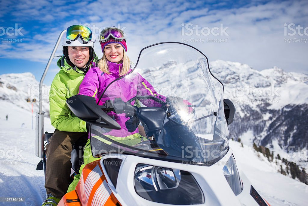 Young couple on a snowmobile ski resort stock photo