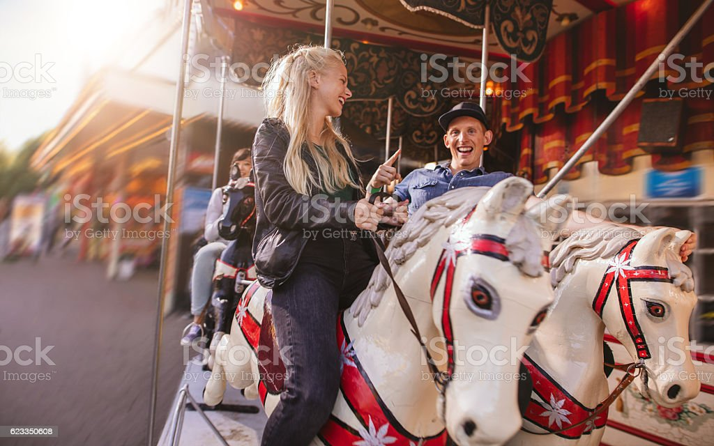 Young couple on amusement park carousel stock photo
