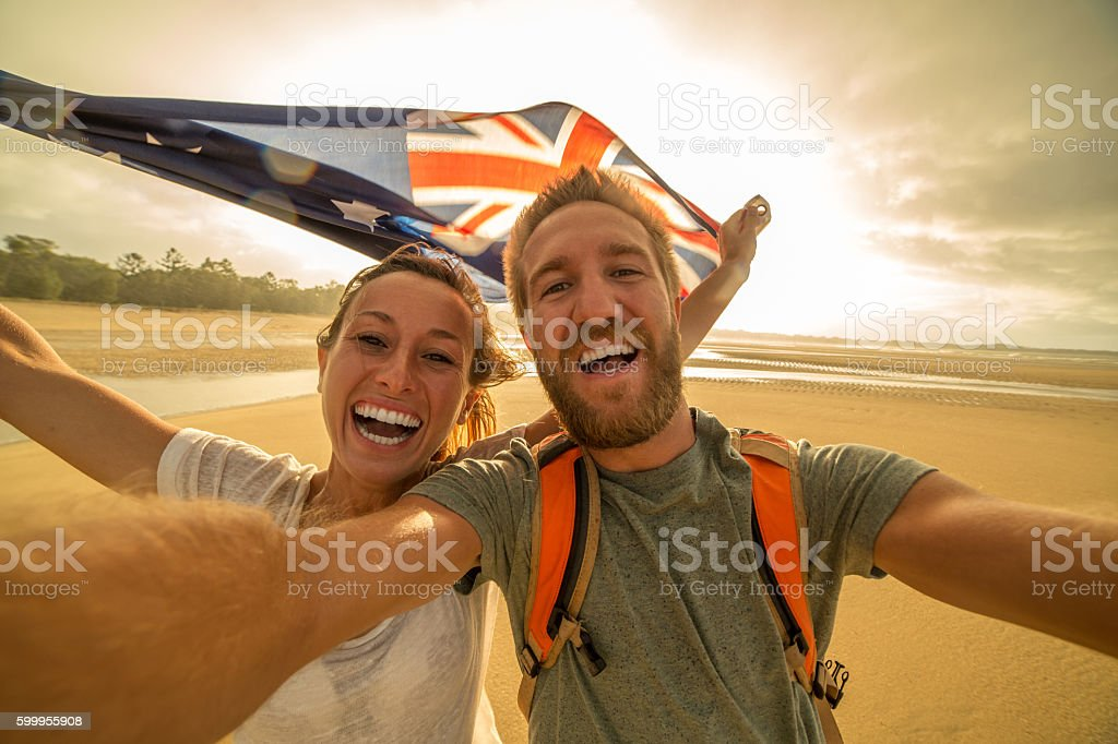 Young couple on beach take selfie portrait with Australian flag stock photo