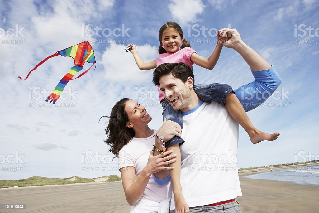 Young couple on beach with little girl flying a kite stock photo