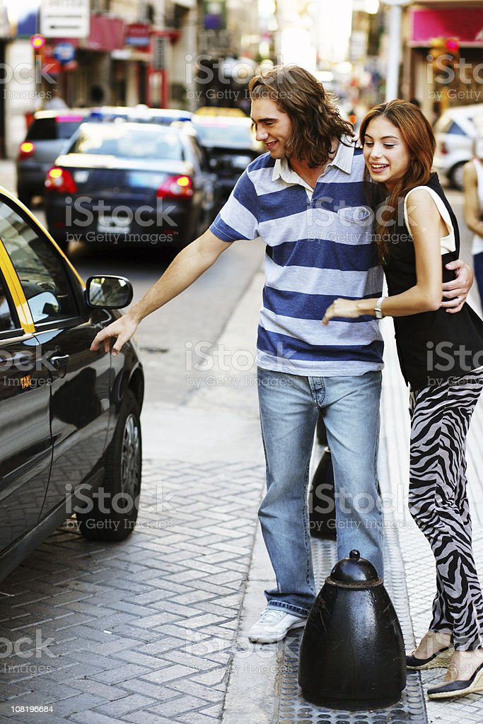 Young Couple on City Street Getting in Taxi royalty-free stock photo