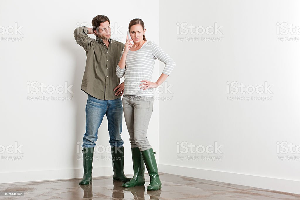 Young couple on flooded floor stock photo