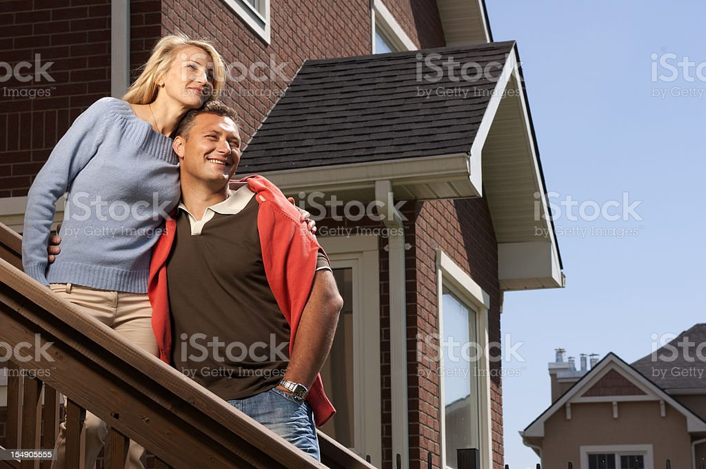 Young couple on front porch of their new suburban house royalty-free stock photo