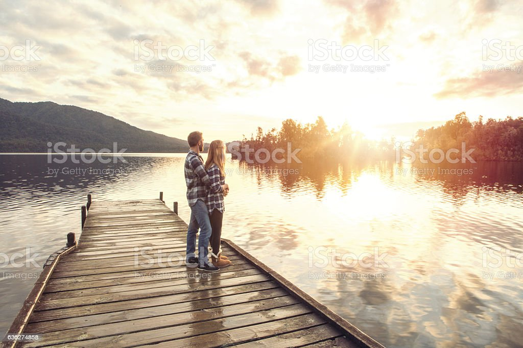 Young couple on lake pier sharing special moment stock photo