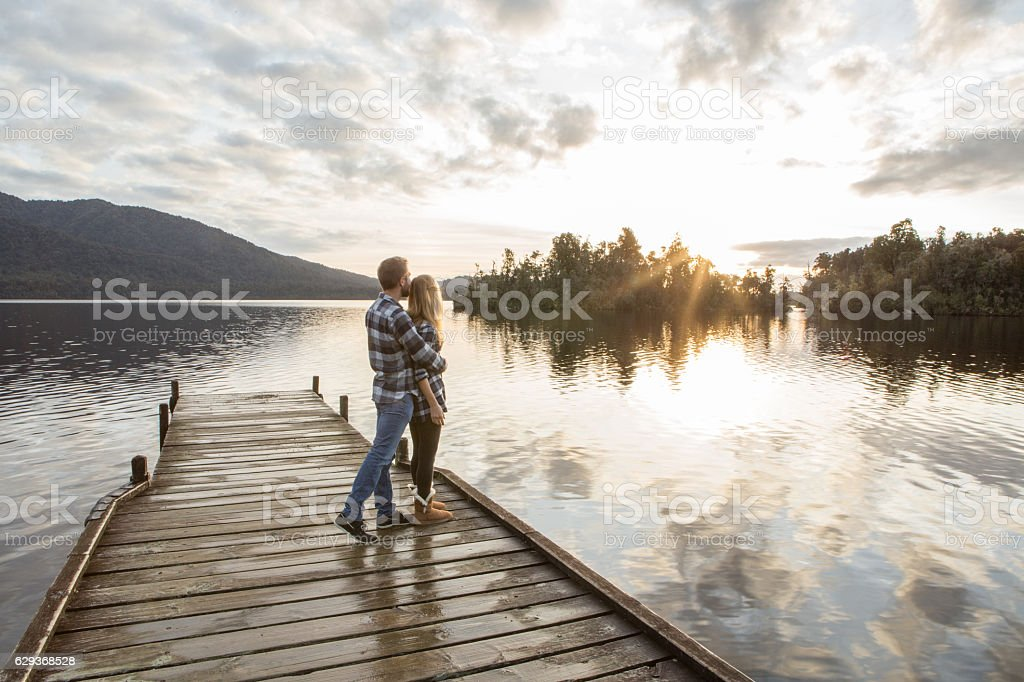 Young couple on lake pier watching sunset stock photo