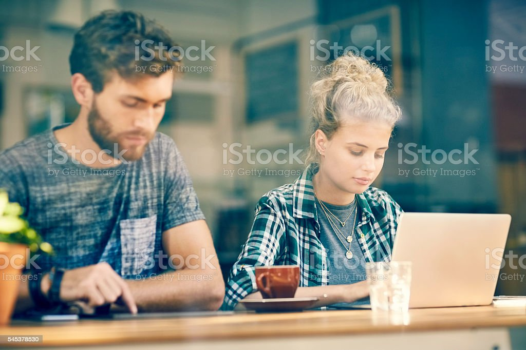 Young Couple On Laptop And Tablet Inside Cafe Window Royalty Free Stock  Photo