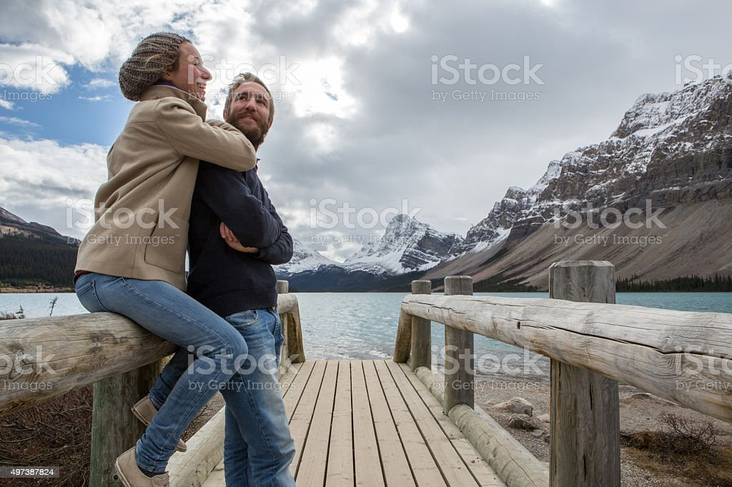 Young couple on log bridge by the lake being affectionate stock photo