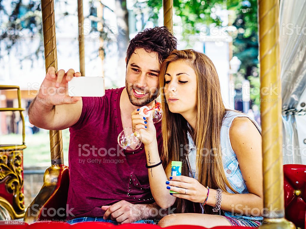Young Couple On Merry Go Round Having A Selfie stock photo
