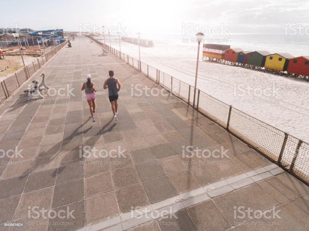 Young couple on morning run at beach promenade stock photo