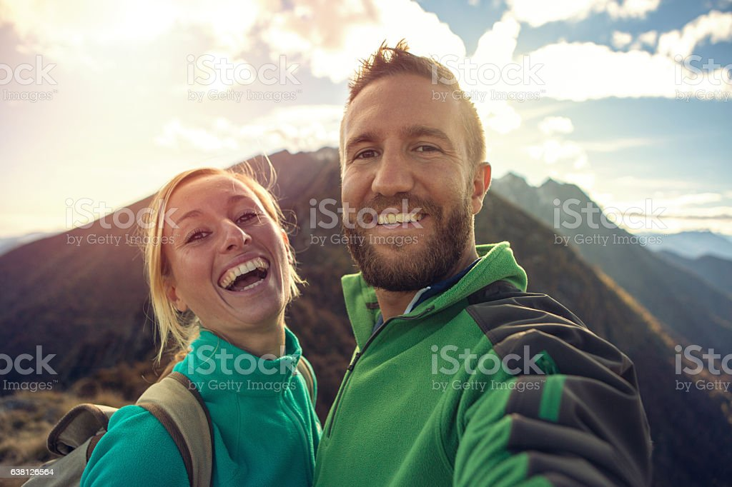 Young couple on mountain top take selfie portrait stock photo