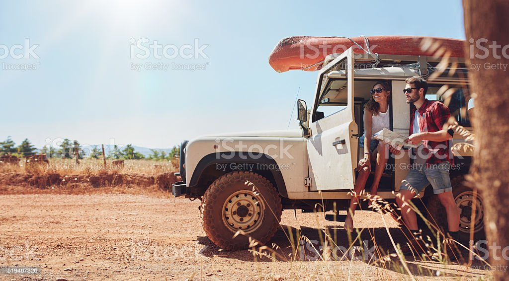 Young couple on road trip reading map for directions stock photo