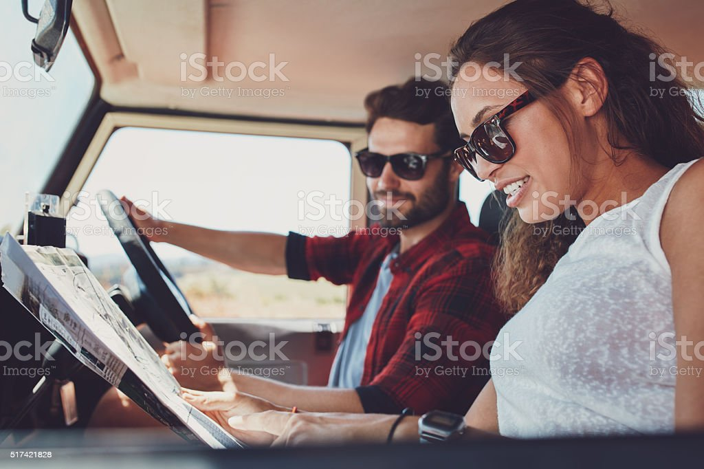 Young couple on roadtrip reading map for directions stock photo