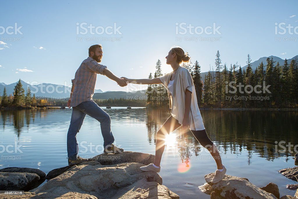 Young couple on rocks by the lake holding hands. stock photo