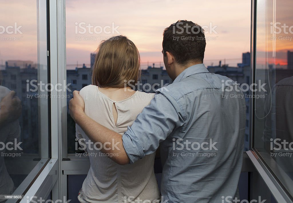 Young couple on the balcony watching sunset royalty-free stock photo