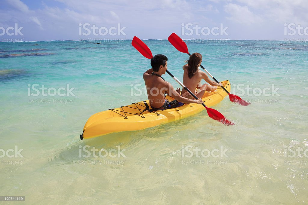 Young couple paddling in a yellow kayak in Hawaii in daytime royalty-free stock photo