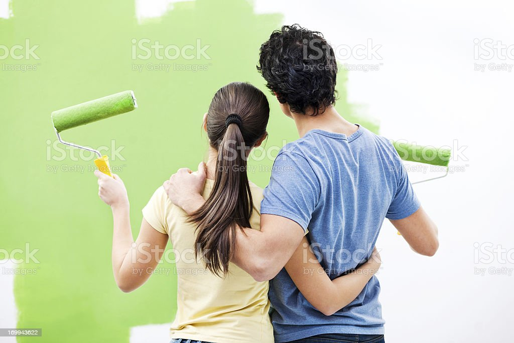 Young couple painting the wall. stock photo