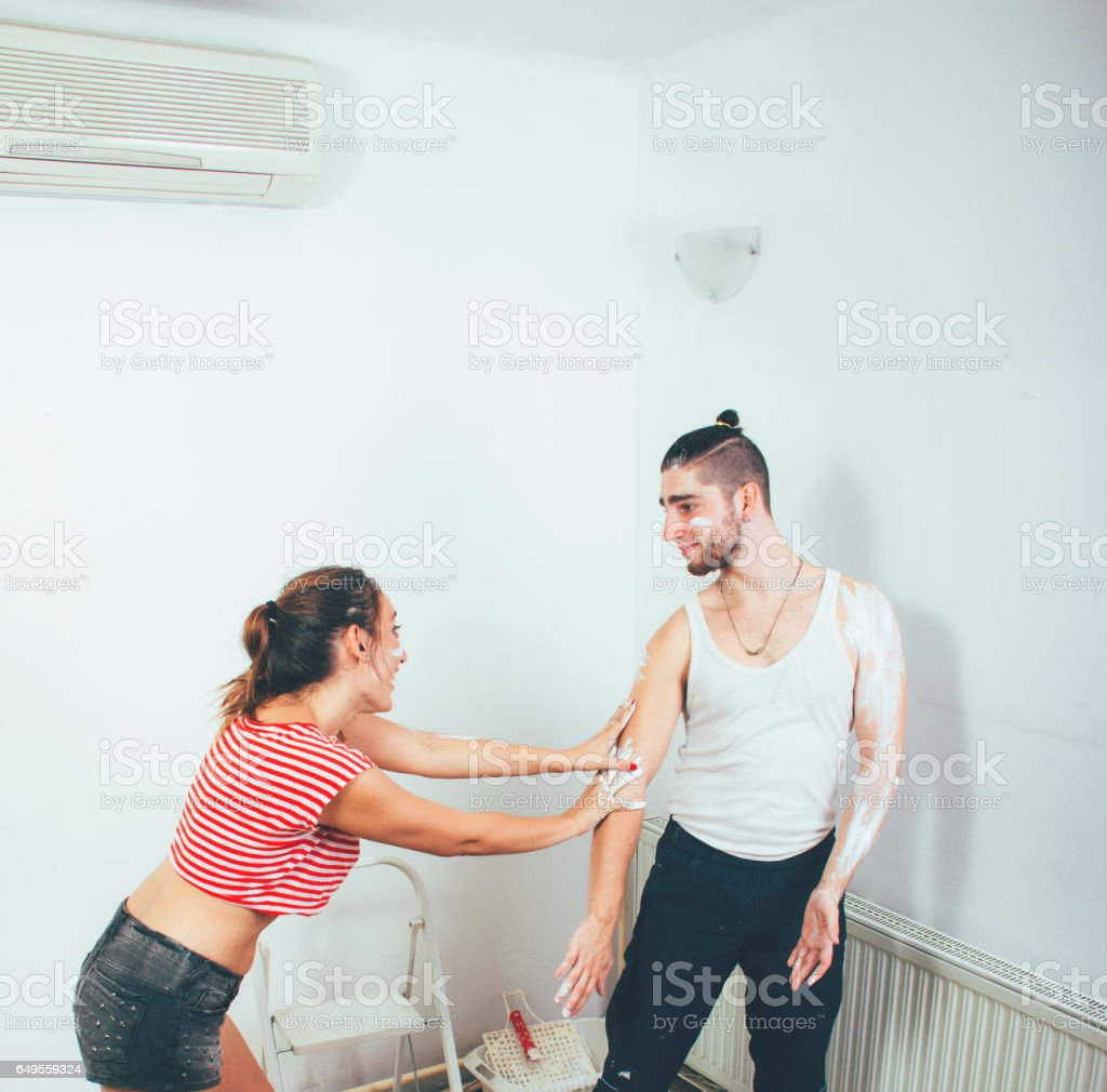 Young couple painting the wall stock photo
