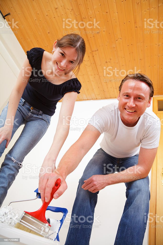 young couple painting the walls in their new apartment royalty-free stock photo