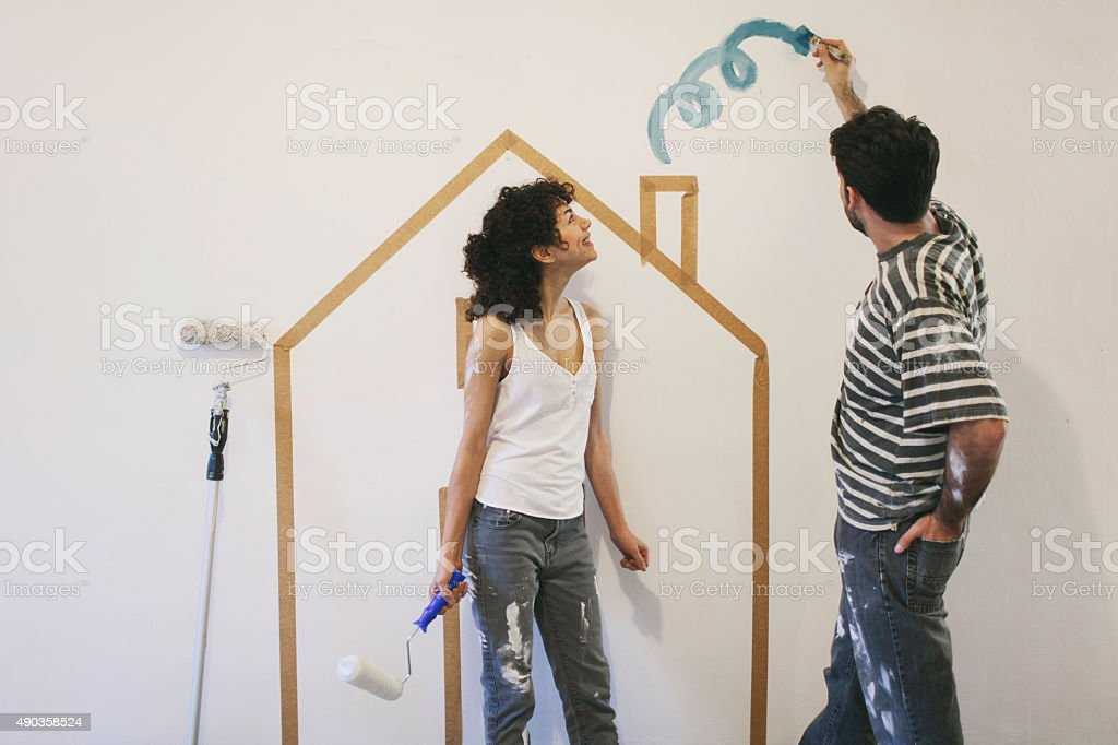 Young couple painting their apartment. stock photo