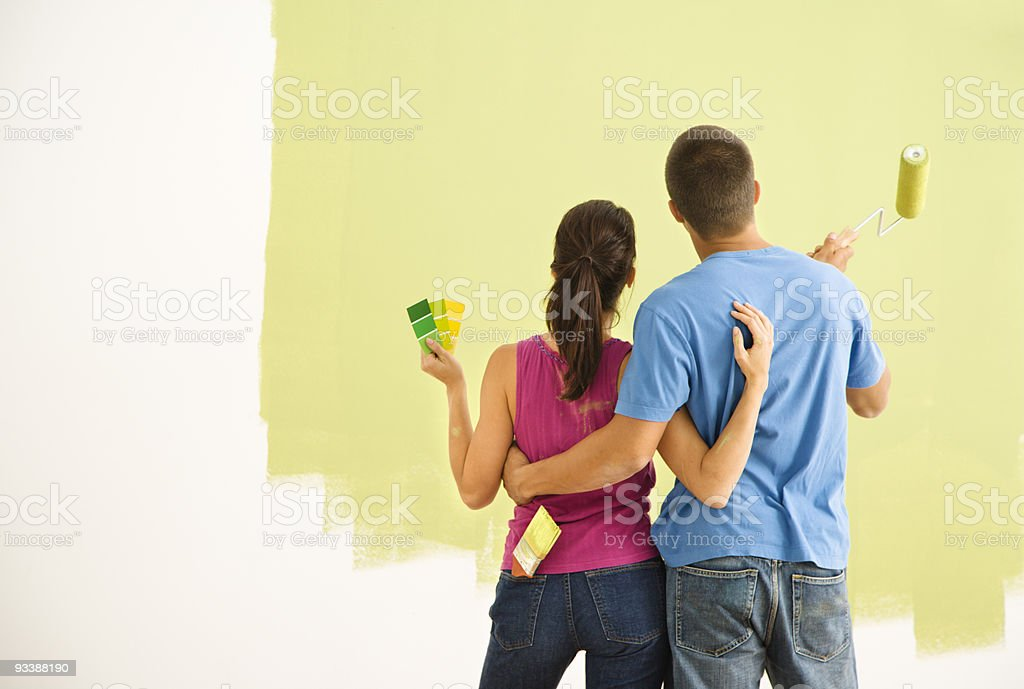 A young couple painting their home together royalty-free stock photo