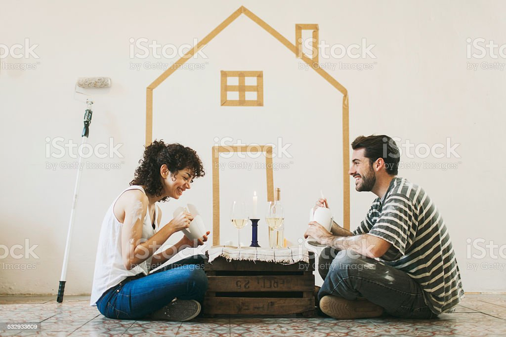 Young couple painting their new apartment. stock photo
