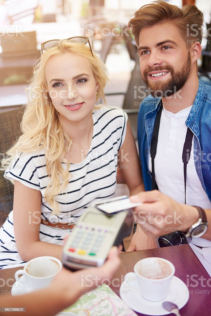 Young couple paying for the coffee stock photo