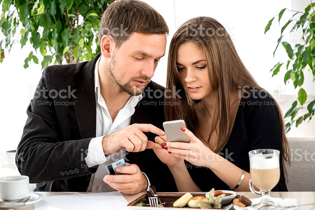 Young couple paying for ther order at the restaurant stock photo