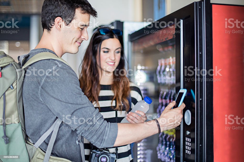 Young couple paying with mobile phone the soft drink stock photo
