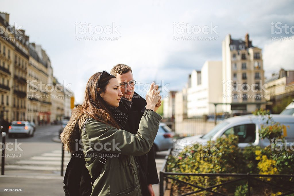 Young couple photographing on the streets of Paris stock photo
