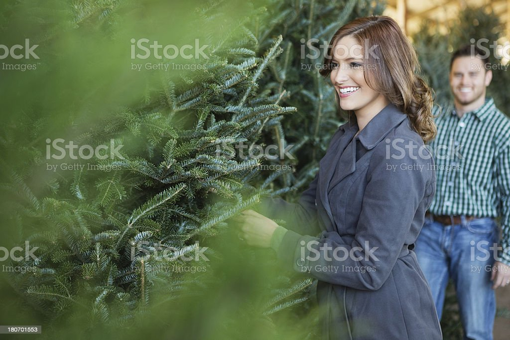 Young couple picking out the perfect Christmas tree together royalty-free stock photo