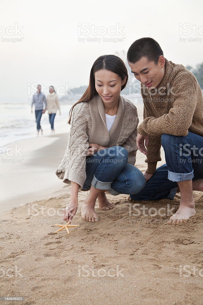 Young Couple Picking Up Starfish on the Beach stock photo