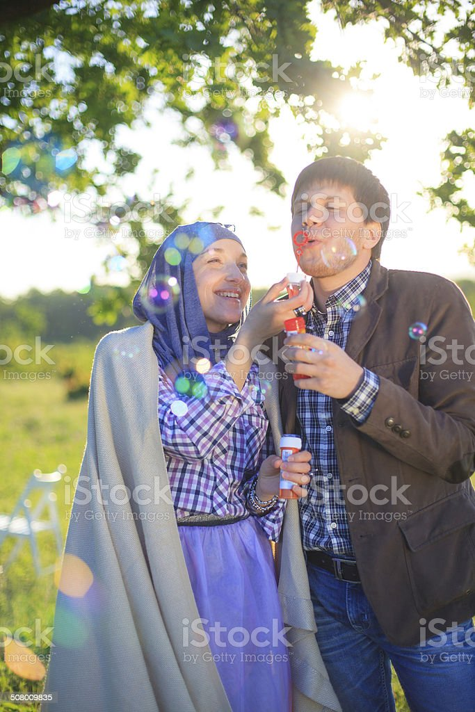 Young couple play together with bubble blower stock photo