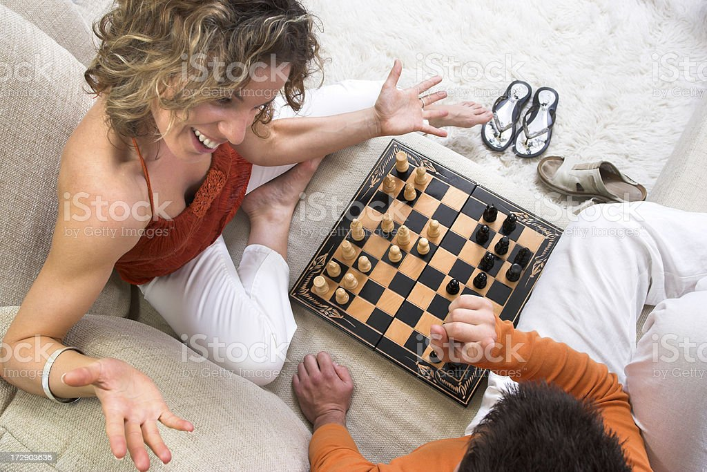 Young couple playing chess at home in the living room royalty-free stock photo