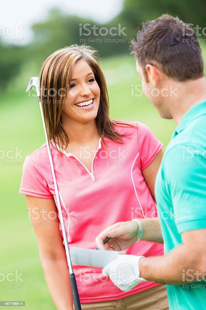 Young couple playing golf together on sunny day stock photo