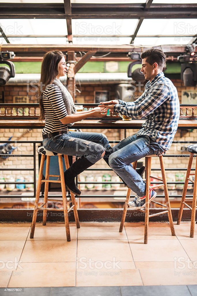 Young couple playing Miss Mary Mack in a cafe. stock photo