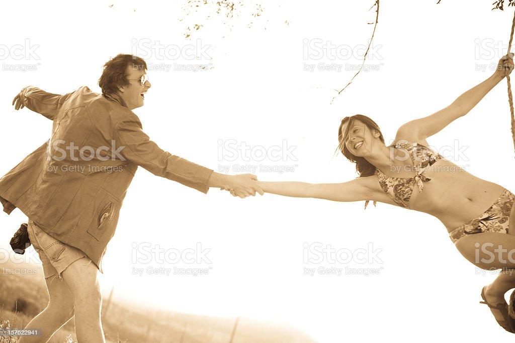 Young couple playing on a rope swing at sunset royalty-free stock photo