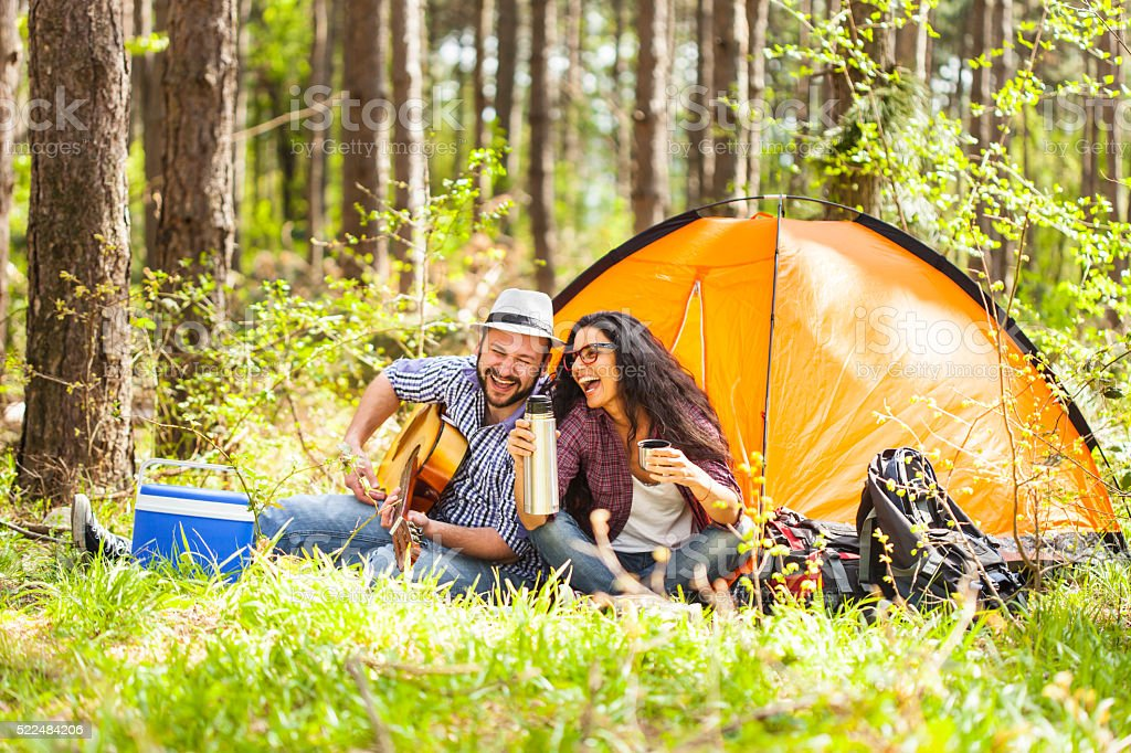 Young couple playing on guitar in the forest stock photo