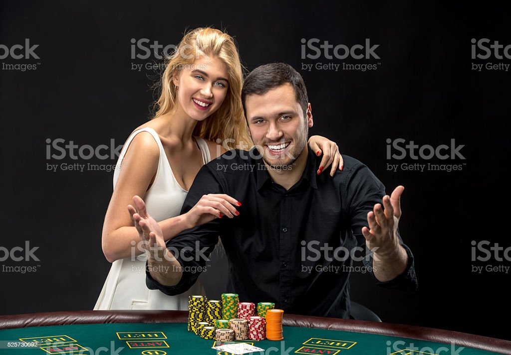 Young couple playing poker have a good time in casino stock photo